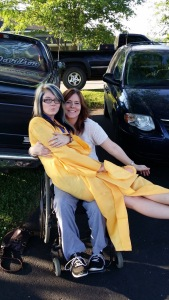 A picture of me in my wheelchair with my youngest daughter sitting in my lap with her cap and gown on