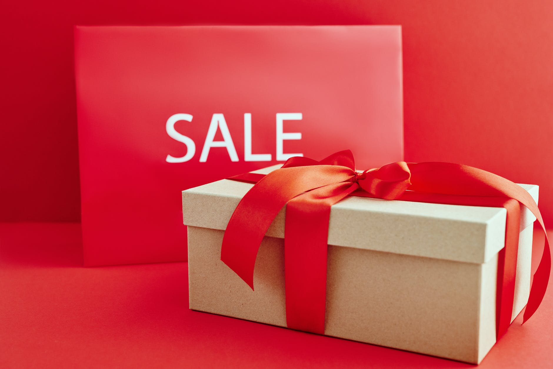 A big gift box with a red bow so you can get the savings when shopping with wish.