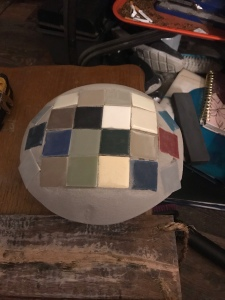 Different colors of square tiles on round concrete surface